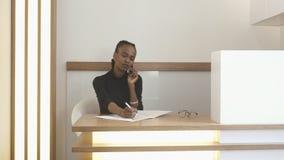 与自然构成的年轻非洲receptiniost与客户谈话通过手机并且填装某事 免版税库存图片