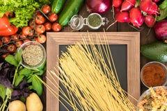 与自然菜、香料和意大利面团的两种类型的食物背景在黑板的 免版税库存照片