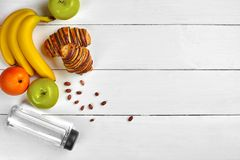 与自由空间的果子早餐在木桌上 新月形面包、香蕉、苹果、坚果和一个瓶水 顶视图 库存照片
