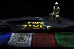 与自由西藏T恤杉和菩萨雕象的祷告旗子 免版税库存照片