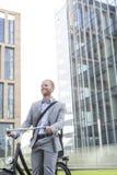 与自行车常设外部办公楼的愉快的商人 免版税图库摄影