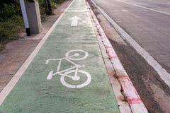 与自行车的标志的自行车道沿高速公路的 骑自行车路径 免版税库存照片