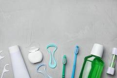与舌头擦净剂的平的被放置的构成和牙关心在灰色背景的产品 库存照片