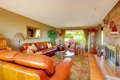 与舒适的皮革沙发的舒适灰色客厅内部 壁炉镶入看法砖墙 库存图片