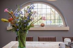 与舒适葡萄酒窗口的五颜六色的花 免版税库存图片
