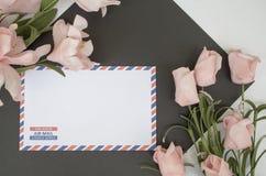 与航空邮件信封和花的平的位置构成 免版税库存图片