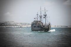 与航行接近海岸的游人的海盗船 图库摄影