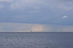 与航行游艇和浮动灯塔的多云海景 库存图片