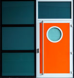 与舷窗窗口的现代橙色金属门 库存照片