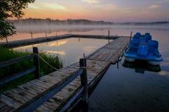 与船坞和小船的有薄雾的Morning湖场面 免版税库存图片