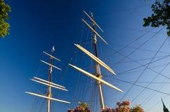 与船游艇寿衣绳索的帆柱有绿色叶子树arou的 免版税库存图片