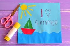 与船的五颜六色的纸牌,海、太阳和词我爱夏天 剪刀和胶浆在淡紫色木背景黏附 库存图片