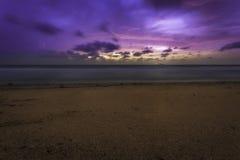 与船的桃红色和紫色海滩日出在天际 免版税库存照片