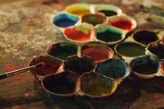 与色板显示和画笔选择聚焦的五颜六色的肮脏的艺术性的桌 免版税库存图片