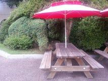 与色的伞的室外木长凳 免版税库存图片