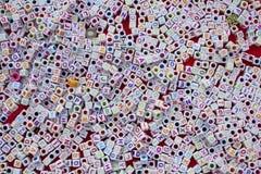 与色的信件和孔的许多白色立方体在红色背景说谎 库存照片
