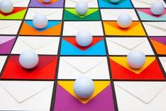 与色的信封和高尔夫球的构成在桌上 库存图片