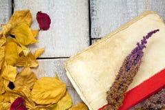 与色的叶子、书和花的秋天背景在木板 免版税图库摄影