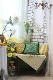 与色的枕头、花瓶和花的客厅内部角落 免版税库存图片