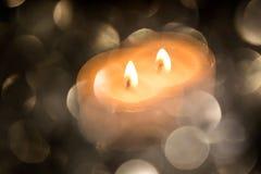 与色的模糊的轻的圈子和一个热的蜡烛的欢乐背景 免版税库存图片