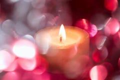 与色的模糊的轻的圈子和一个热的蜡烛的欢乐背景 库存图片
