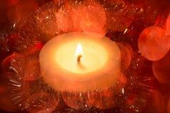 与色的模糊的轻的圈子和一个热的蜡烛的欢乐背景 免版税库存照片