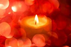 与色的模糊的轻的圈子和一个热的蜡烛的欢乐背景 库存照片
