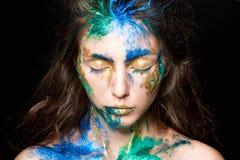 与色的油漆的美丽的面孔在黑背景 免版税库存照片