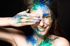 与色的油漆的美丽的面孔在黑背景 免版税库存图片