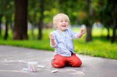 与色的白垩的愉快的小孩男孩图画在沥青 免版税库存照片