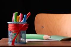 与色的笔的一块玻璃在一张木桌上 文具集合 概念:回到学校 图库摄影