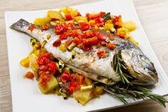 与色的菜的被烘烤的鱼 免版税库存照片