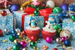 与色的装饰由糖果店乳香树脂做的雪人和企鹅的圣诞节杯形蛋糕 库存照片