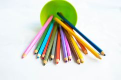 与色的铅笔的一块绿色塑料玻璃 免版税库存图片