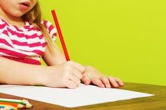 与色的铅笔的一张小女孩图画 免版税库存照片