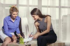 与色的铅笔的两个女孩凹道剪影 免版税库存图片