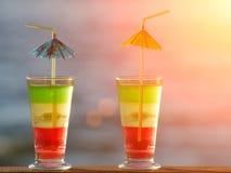 与色的鸡尾酒的两块玻璃接近在海背景,定调子 免版税图库摄影