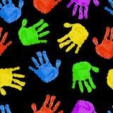 与色的handprints的无缝的黑暗的背景 免版税库存图片
