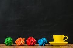 与色纸球的黄色咖啡杯小组 库存照片