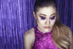 与艺术性的美好的迷人的模型组成,闪烁泪花、波浪马尾辫和上面摆在反对闪亮金属片的由紫色闪烁制成 免版税图库摄影
