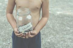 与节约金钱的Childern在玻璃和葡萄酒fi的教育的 库存图片