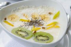 与芒果chia猕猴桃的酸奶在与白色桌布的白色陶器 免版税库存照片