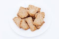 与芝麻籽的自创曲奇饼在一块白色板材 库存照片