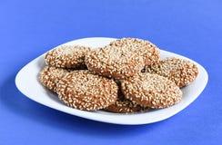 与芝麻籽的麦甜饼在紫罗兰色ba的一个白色盘 免版税库存图片
