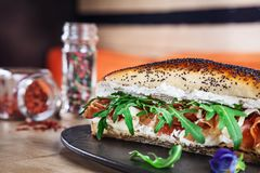 与芝麻菜、奶油奶酪和熏火腿的三明治在黑暗的石板材 与拷贝空间的新鲜的大三明治 便当,快餐 图库摄影