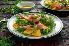 与芝麻菜、帕尔马火腿、橄榄油、南瓜籽和草本的新鲜的鲜美柿子沙拉 秋天,冬天健康食物 图库摄影
