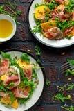 与芝麻菜、帕尔马火腿、橄榄油、南瓜籽和草本的新鲜的鲜美柿子沙拉 秋天,冬天健康食物 库存照片