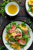 与芝麻菜、帕尔马火腿、橄榄油、南瓜籽和草本的新鲜的鲜美柿子沙拉 秋天,冬天健康食物 免版税库存图片