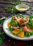 与芝麻菜、帕尔马火腿、橄榄油、南瓜籽和草本的新鲜的鲜美柿子沙拉 秋天,冬天健康食物 免版税库存照片