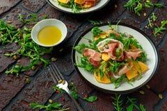 与芝麻菜、帕尔马火腿、橄榄油、南瓜籽和草本的新鲜的鲜美柿子沙拉 秋天,冬天健康食物 库存图片